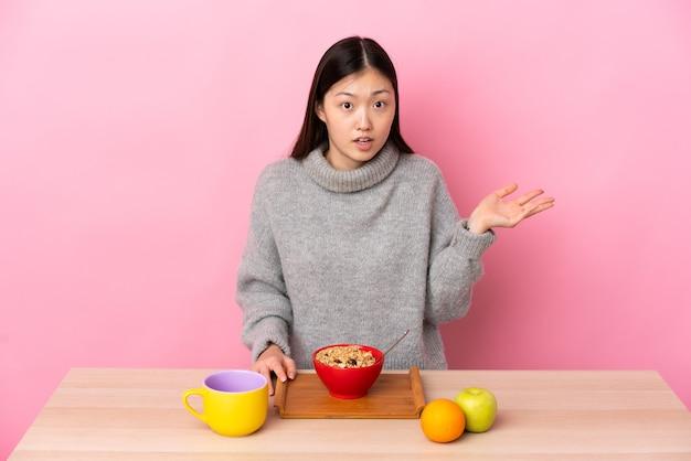 疑いのジェスチャーを作るテーブルで朝食を食べている若い中国の女の子