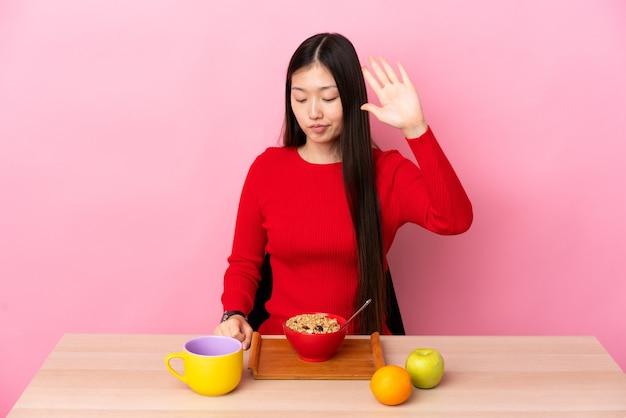 Молодая китаянка завтракает за столом, делая жест стоп и разочарована