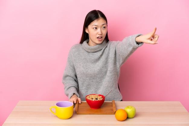 離れて指しているテーブルで朝食を食べている若い中国の女の子