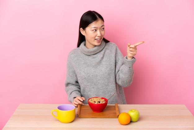 젊은 중국 소녀 옆에 손가락을 가리키고 제품을 제시하는 테이블에서 아침을 먹고