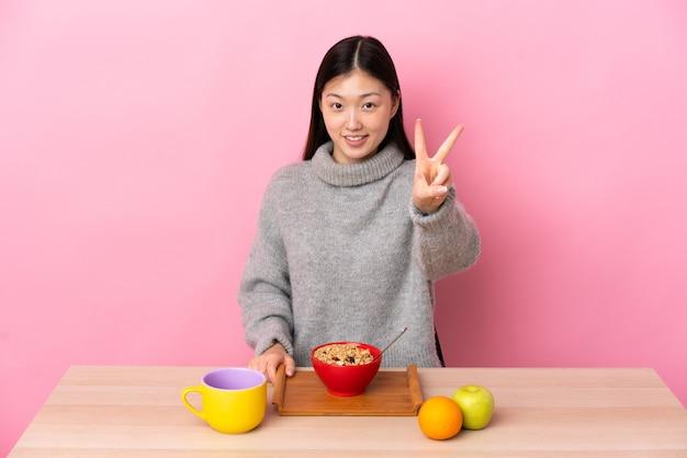 웃 고 승리 기호를 보여주는 테이블에서 아침을 먹고 젊은 중국 소녀