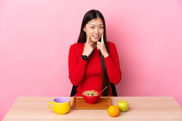 행복하고 즐거운 표정으로 웃는 테이블에서 아침을 먹고 젊은 중국 소녀