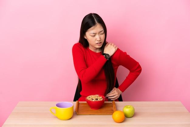 努力したために肩の痛みに苦しんでいるテーブルで朝食をとっている若い中国の女の子