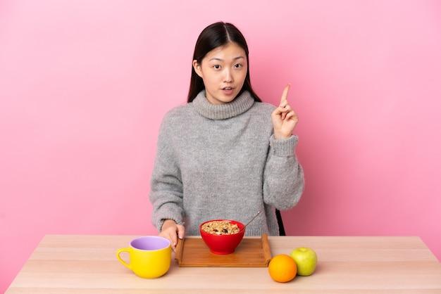 손가락을 가리키는 아이디어를 생각하는 테이블에서 아침을 먹고 젊은 중국 소녀