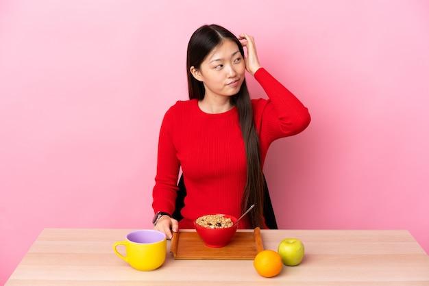 アイデアを考えてテーブルで朝食をとっている若い中国の女の子