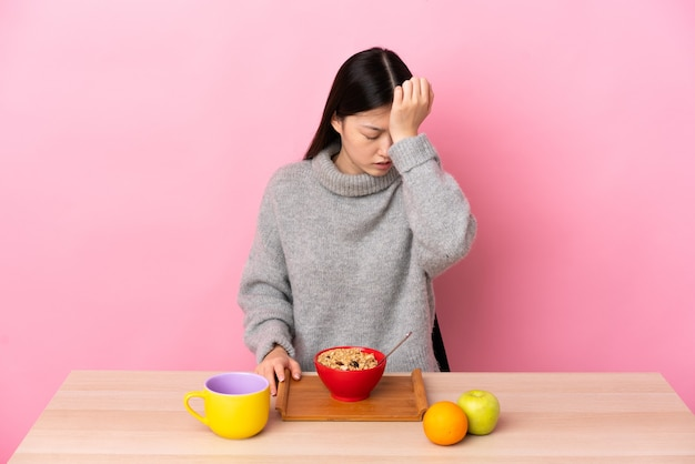 Young chinese girl  having breakfast in a table with headache