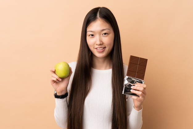 チョコレート タブレットとアップルを取って若い中国人の女の子の隔離された背景