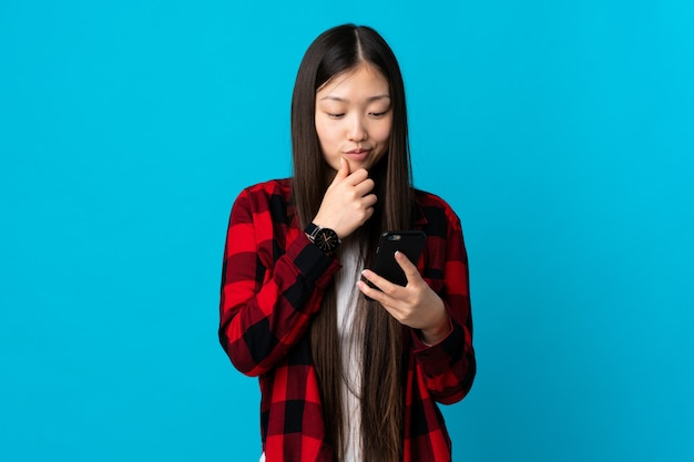 Young chinese girl over isolated blue background thinking and sending a message