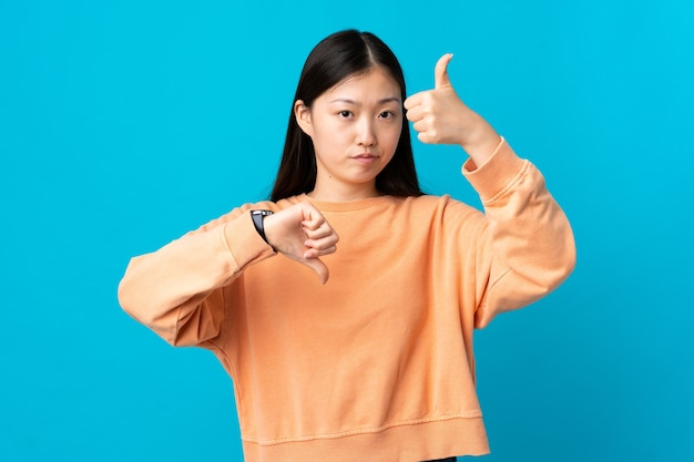 Young chinese girl on isolated blue making good-bad sign. undecided between yes or not