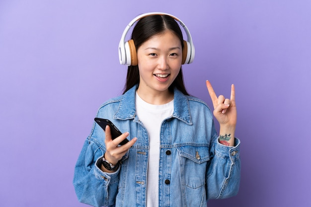 Young chinese girl over isolated purple listening music with a mobile making rock gesture