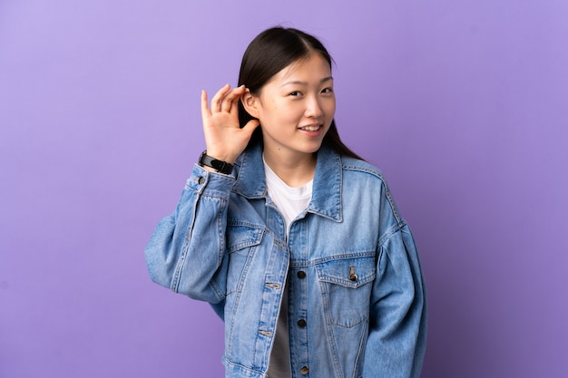 Young chinese girl over isolated purple wall listening to something by putting hand on the ear