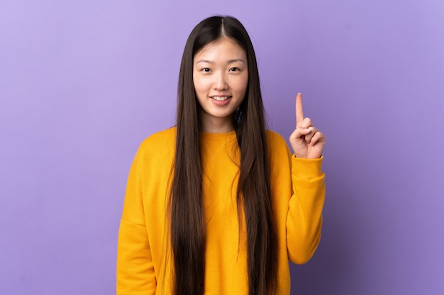 Young chinese girl over isolated purple wall pointing up a great idea