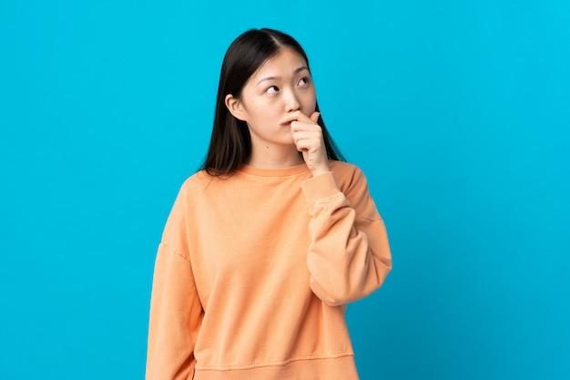 Молодая китайская девушка на изолированных синий, имея сомнения и смущать выражение лица
