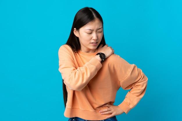 Молодая китаянка на синем фоне страдает от боли в плече из-за того, что приложила усилие