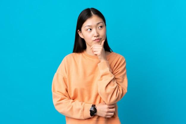 Молодая китайская девушка на изолированной сини думая идея пока смотрящ вверх