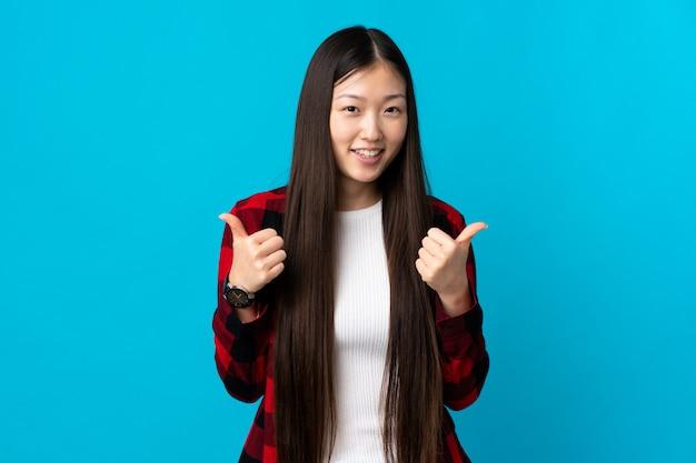 Молодая китайская девушка на изолированной сини с большими пальцами руки вверх показывать и усмехаться