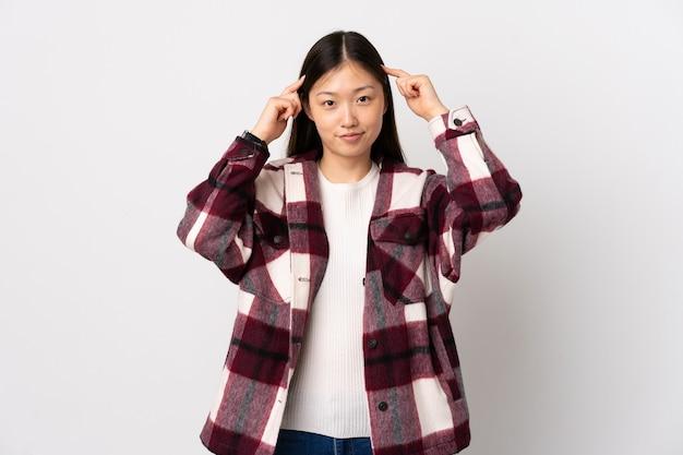 의심과 생각을 갖는 고립 된 흰색에 젊은 중국 소녀