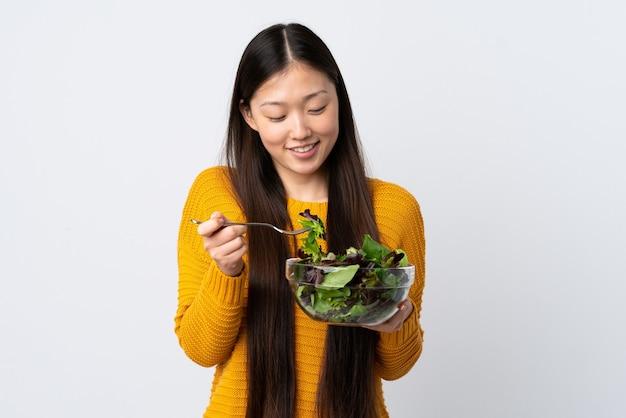 Молодая китаянка на изолированном белом держит миску салата с счастливым выражением лица