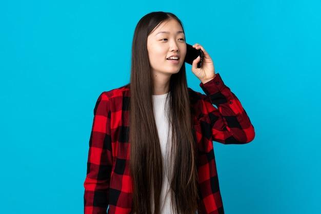 携帯電話と会話を続ける青の若い中国の女の子