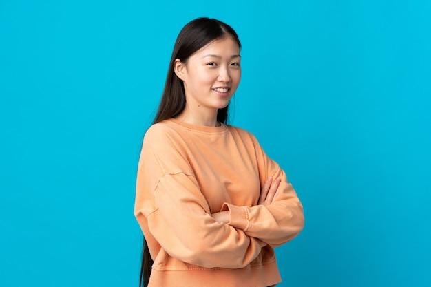 腕を組んで、楽しみにして青い上の若い中国の女の子