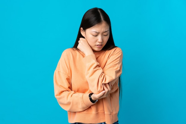 Молодая китаянка над синим с болью в локте