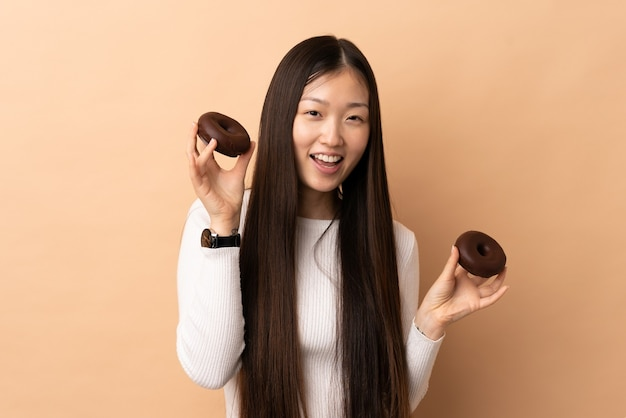 幸せな表情でドーナツを保持している孤立した背景上の若い中国の女の子