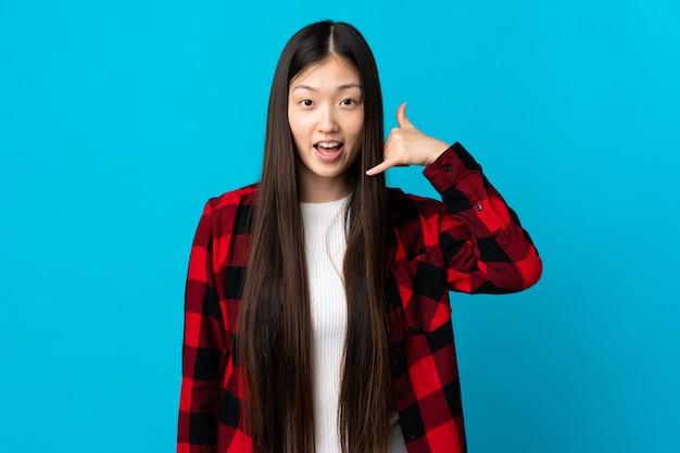 電話ジェスチャーを作る孤立した青い背景の上の若い中国の女の子。コールバックサイン