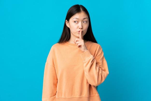 Молодая китаянка на изолированном синем фоне показывает знак жеста молчания, кладя палец в рот
