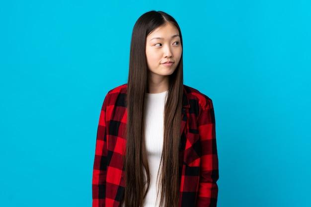 측면을 보면서 의심을 갖는 고립 된 파란색 위에 젊은 중국 소녀