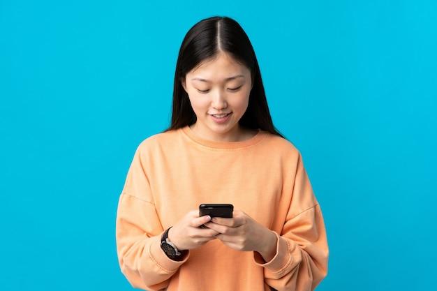 モバイルでメッセージを送信する孤立した青の上の若い中国の女の子