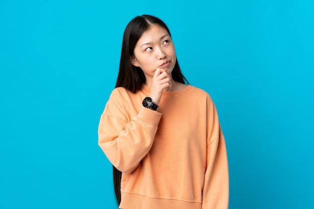 고립 된 파란색 벽에 젊은 중국 여자와 올려