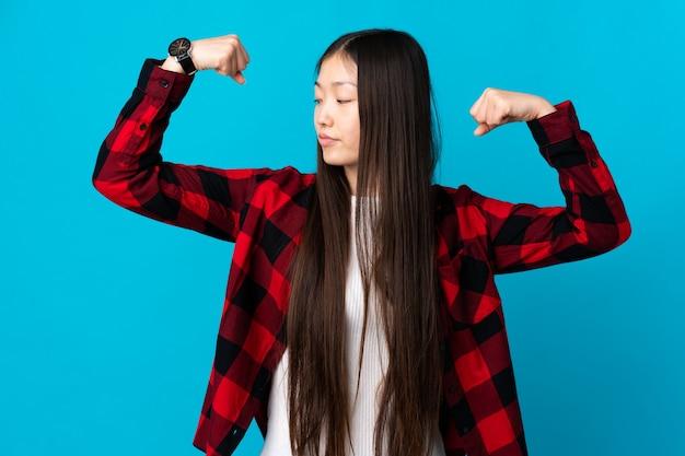 Молодая китаянка над изолированной синей стеной делает сильный жест
