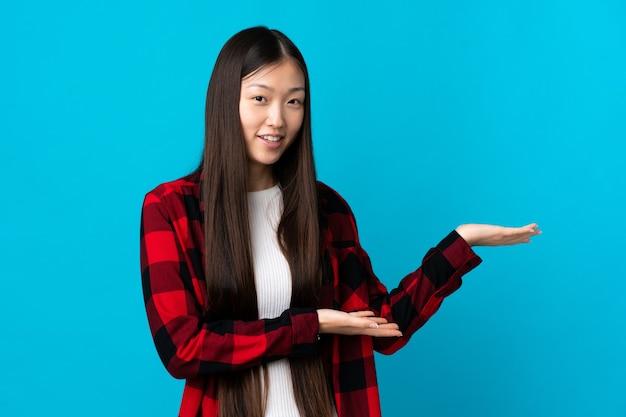 孤立した青い壁の上の若い中国の女の子は、来て招待するために手を横に伸ばします