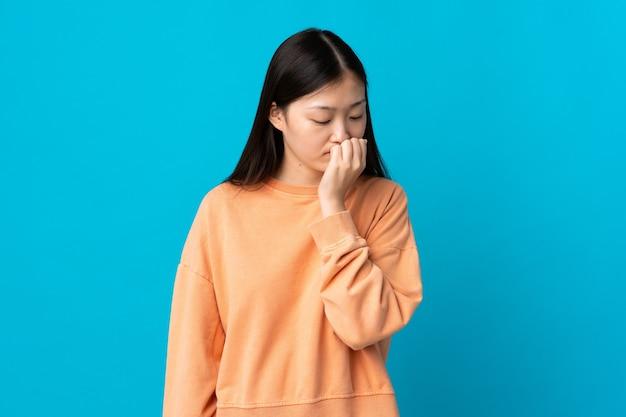 의심을 가지고 고립 된 파란색 벽 위에 젊은 중국 여자