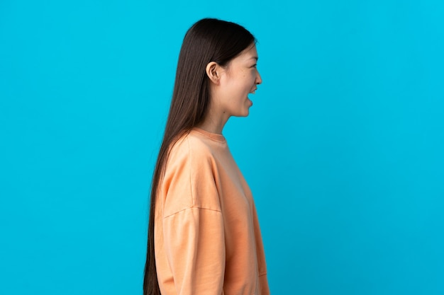 横向きの位置で笑っている孤立した青い壁の上の若い中国の女の子