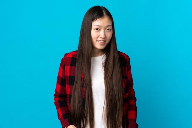 笑っている孤立した青い壁の上の若い中国の女の子