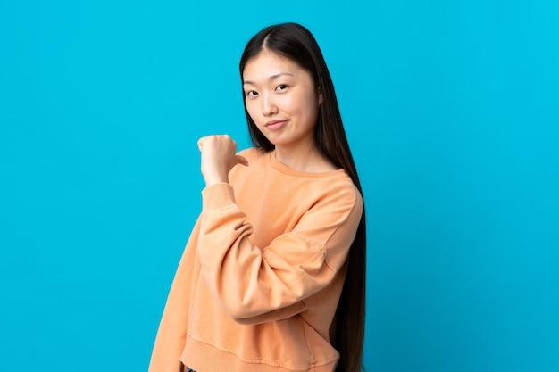 誇りと自己満足の孤立した青い壁の上の若い中国の女の子