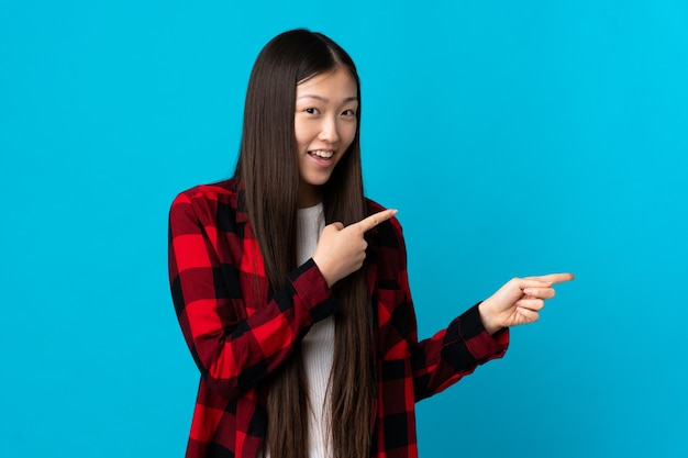 孤立した青い壁の上の若い中国の女の子は驚いて、側を指しています