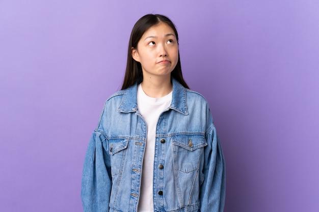 Молодая китайская девушка над изолированным пурпуром и смотреть вверх
