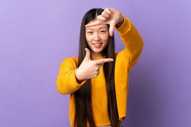 孤立した紫色のフォーカシング顔の上の若い中国人の女の子。フレーミングシンボル