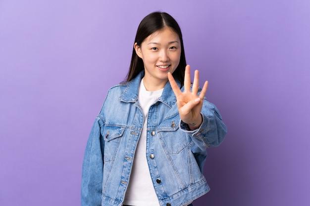 Молодая китайская девушка над изолированным фиолетовым счастливым и подсчитывать 4 с пальцами