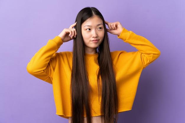 Молодая китайская девушка над изолированным пурпуром имея сомнения и думая