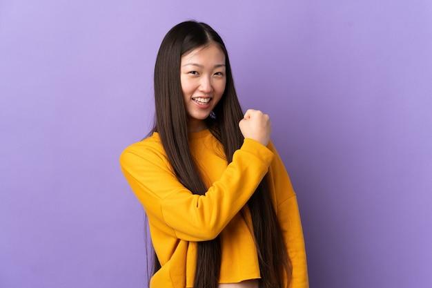 勝利を祝う孤立した紫色の壁の上の若い中国の女の子