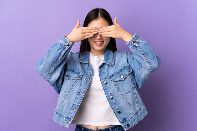 手と笑顔で目を覆う孤立した紫色の壁の上の若い中国の女の子