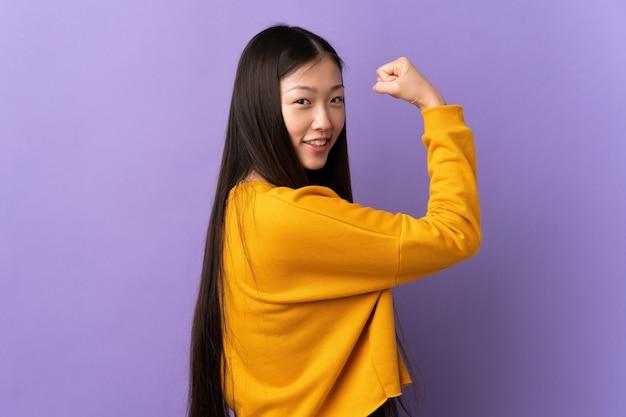 強いジェスチャーをしている孤立した紫色の壁の上の若い中国の女の子