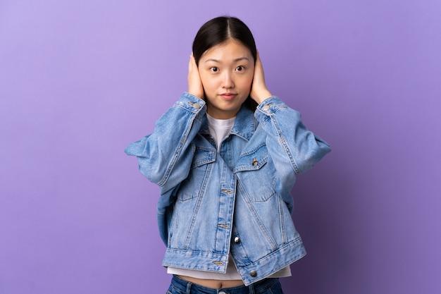 欲求不満と耳を覆っている孤立した紫色の壁の上の若い中国の女の子