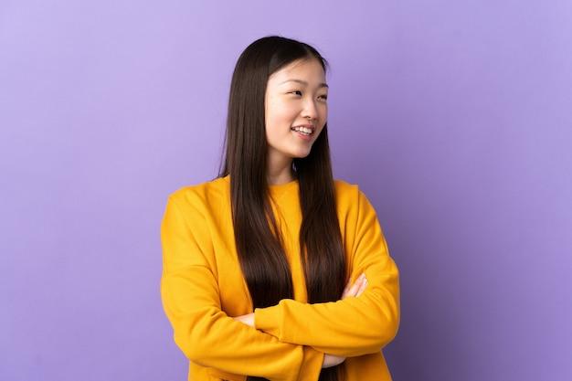 Молодая китаянка над изолированной фиолетовой стеной счастлива и улыбается