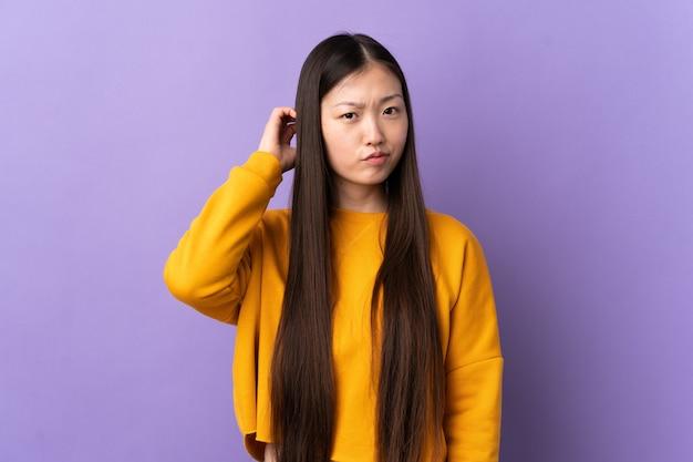 의심을 가지고 고립 된 보라색 벽 위에 젊은 중국 여자