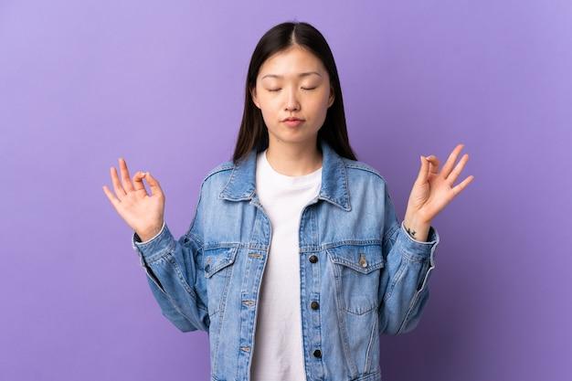 禅のポーズで孤立した紫色の壁の上の若い中国の女の子