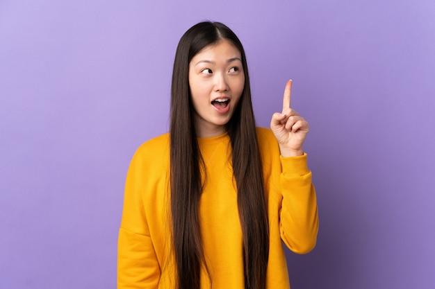 Молодая китаянка над изолированной фиолетовой стеной, намереваясь найти решение, подняв палец вверх